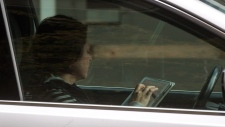 A woman uses an iPad while behind the wheel of a vehicle stopped in traffic at a red light in downtown Vancouver, B.C., on Monday October 20, 2014. (THE CANADIAN PRESS/Darryl Dyck)