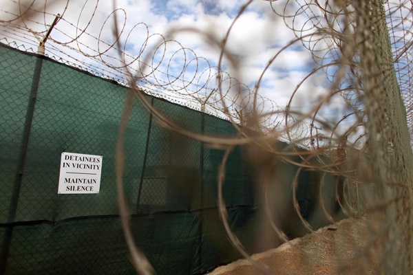 A notice hangs on a razor wire fence at the Guantanamo detention center on the U.S. Naval Base in Guantanamo Bay, Cuba, Wednesday, Jan. 21, 2009. (AP / Brennan Linsley)