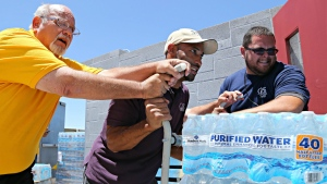 This Tuesday, June 14, 2016 photo Leo Block, left, Matari Phason, center, and Brian Juarez, right, push part of a shipment of 20,000 water bottles donated by Yellow Cab of Phoenix to Central Arizona Shelter Services, Arizona's largest homeless shelter, to help prepare for the summer heat in Phoenix, Ariz. (AP Photo / Ryan Van Velzer)