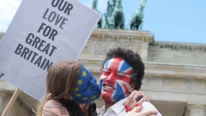 "A young couple with faces paint in European, left, and British colors, pose with a sign ""Our Love For Great Britain"" during a Kiss Marathon event at Brandenburg Gate in Berlin, Germany, Sunday June 19, 2016 to support the ' Remain' voters in Britain's referendum. (Joerg Carstensen/dpa via AP)"