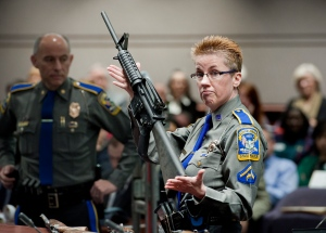 Firearms training unit Det, Barbara J. Mattson, of the Connecticut State Police, holds up a Bushmaster AR-15 rifle, the same make and model of gun used by Adam Lanza in the Sandy Hook School shooting, for a demonstration during a hearing of a legislative subcommittee reviewing gun laws, at the Legislative Office Building in Hartford, Conn. on Jan. 28, 2013. (AP / Jessica Hill)