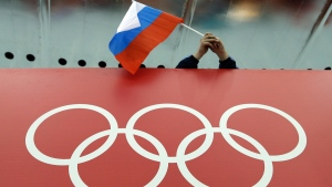 A Russian skating fan holds the country's national flag over the Olympic rings in Sochi, Russia, on Feb. 18, 2014. (David J. Phillip / AP)