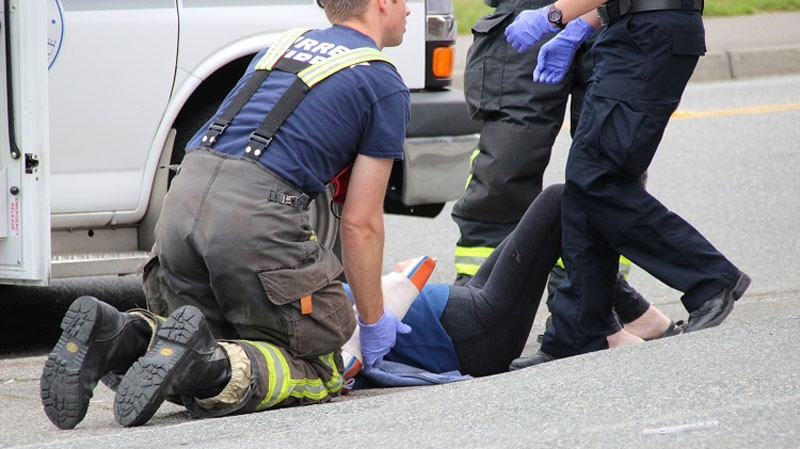 Paramedics and fire fighters help a woman who was attacked by a dog in Surrey on June 20, 2016. (CTV)