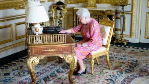 Queen Elizabeth II tweeting on a tablet in the Drawing Room in Windsor Castle, Windsor, England, on June 21, 2016. (Buckingham Palace via AP)