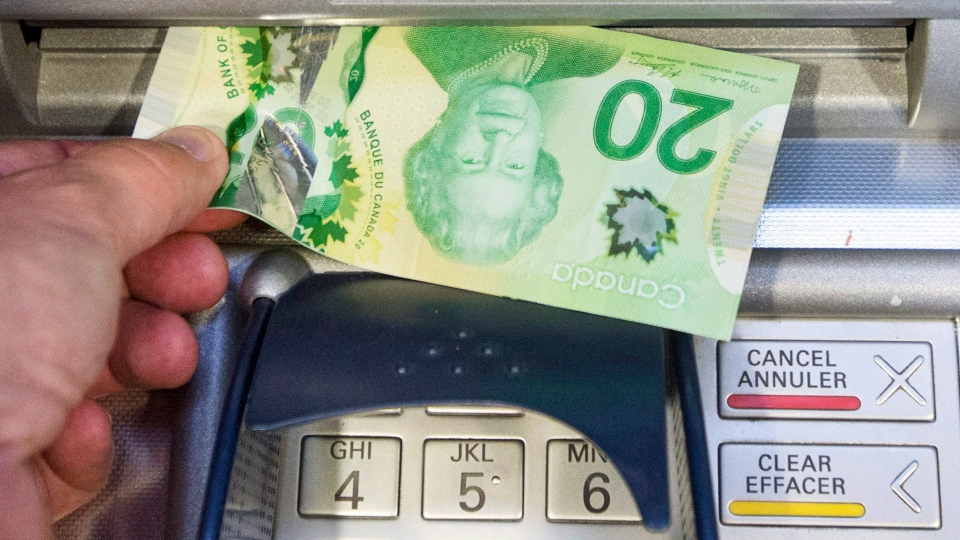 Money is removed from a bank machine in Montreal, Monday, May 30, 2016.(Ryan Remiorz / THE CANADIAN PRESS)