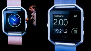 A man walks between two screens displaying new smart watches from fitbit at CES International, Thursday, Jan. 7, 2016, in Las Vegas. Thousands of gadget companies from around the world gather this week in Las Vegas to show off their latest items. (AP Photo/Gregory Bull)