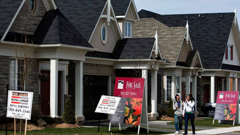 People walk past new homes that are for sale in Oakville, Ont., in this file photo. (THE CANADIAN PRESS/Nathan Denette)