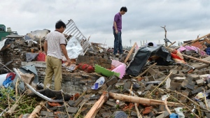 Residents look for belongings in the rubble of a destroyed home in Funing county in Yancheng city in eastern China's Jiangsu Province on Friday, June 24, 2016. (Chinatopix)
