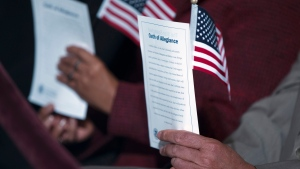 "In this Dec. 15, 2015 file photo, participants hold the ""Oath of Allegiance"" and American flags during a naturalization ceremony attended by President Barack Obama at the National Archives in Washington. (AP Photo/Evan Vucci)"