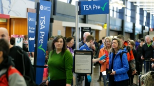 In this March 17, 2016, file photo, travelers authorized to use the Transportation Security Administration's PreCheck expedited security line at Seattle-Tacoma International Airport in Seattle have their documents checked by TSA workers. (AP Photo/Ted S. Warren)