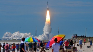Hundreds of people pack the Canaveral national seashore's Playalinda Beach as a United Launch Alliance Atlas V rocket, carrying a U.S. Navy communications satellite, lifts off from Complex 41 at the Cape Canaveral Air Force Station, Friday, June 24, 2016, in Cape Canaveral, Fla. (Craig Rubadoux/Florida Today via AP)