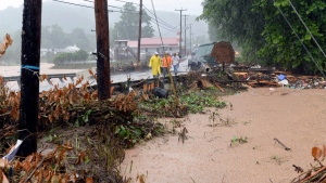 In this photo made from video, debris from the Jordan Creek near Clendenin, W.Va., piles up against a culvert along U.S. 119 on Thursday night June 23, 2016, just before the creek's entry into the Elk River. (Chris Dorst/Gazette-Mail via AP)