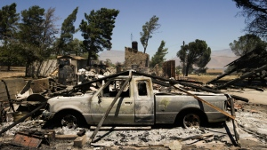 A pickup truck destroyed by a wildfire sits on a burned down property, near Lake Isabella, Calif., on Friday, June 24, 2016. The wildfires have killed two people. (AP Photo/Jae C. Hong)