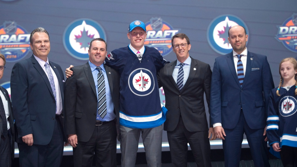 Patrik Laine, second overall pick, stands on stage with members of the Winnipeg Jets management team at the NHL draft in Buffalo, N.Y., on Friday, June 24, 2016. (THE CANADIAN PRESS/Nathan Denette)