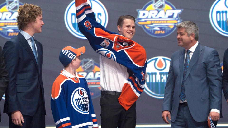 Jesse Puljujarvi, fourth overall pick, pulls on his sweater as he stands on stage with members of the Edmonton Oilers management team at the NHL draft in Buffalo, N.Y., on Friday, June 24, 2016. (THE CANADIAN PRESS/Nathan Denette)