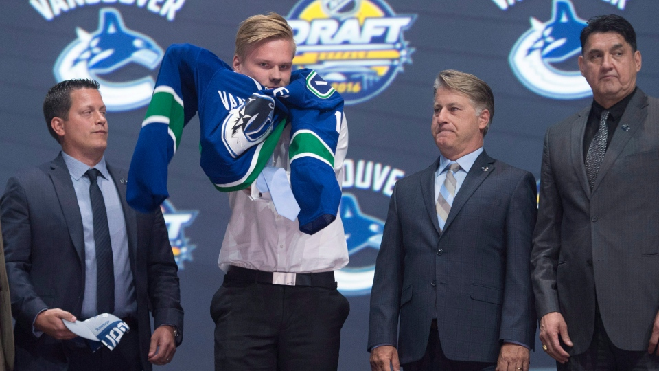 Olli Juolevi, fifth overall pick, puts on Canucks sweater at the NHL draft in Buffalo, N.Y., on Friday, June 24, 2016. (THE CANADIAN PRESS/Nathan Denette)