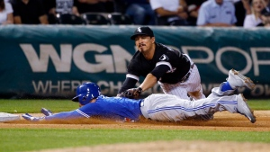 Toronto Blue Jays' Darwin Barney, bottom, slides safely into third base as Chicago White Sox third baseman Tyler Saladino applies a late tag during the ninth inning of a baseball game in Chicago on Friday, June 24, 2016. The White Sox won 3-2. (AP Photo / Nam Y. Huh)
