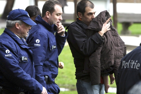 An unidentified man walks away with a child after a stabbing incident at a daycare center in Dendermonde, Belgium, on Friday, Jan. 23, 2009. (AP / Alain Sprimont)