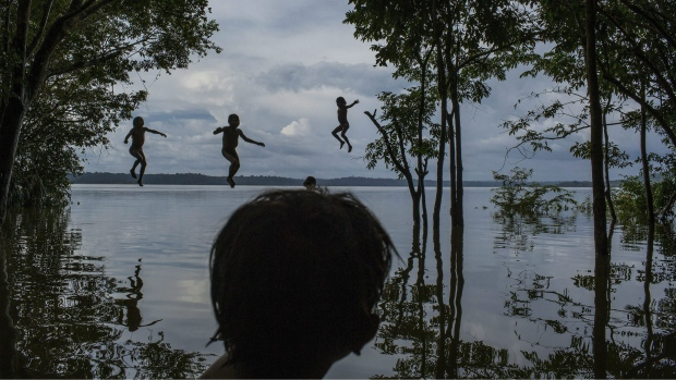 Indigenous Munduruku children playing in the Tapajos river in the tribal area of Sawre Muybu, Itaituba, Brazil, Feb. 10, 2015.  (Mauricio Lima/The New York Times, World Press Photo via AP)