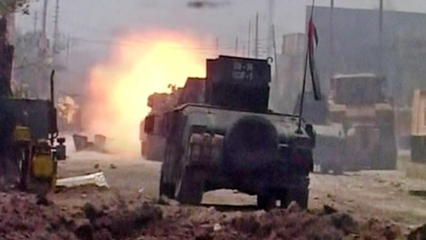 """This image made from Associated Press video shows, A tank fires during clashes in Fallujah, Iraq, Sunday, June 26, 2016. A senior Iraqi commander declared that the city of Fallujah was """"fully liberated"""" from Islamic State group militants on Sunday, after a more than monthlong military operation. (AP Video via AP)"""