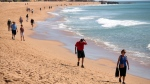 In this picture taken March 1, 2016, People walk along the beach in Albufeira, in southern Portugal's Algarve region. (AP / Armando Franca)