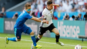 Germany's Julian Draxler, right, challenges for the ball with Slovakia's Peter Pekarik during the Euro 2016 round of 16 soccer match between Germany and Slovakia, at the Pierre Mauroy stadium in Villeneuve d'Ascq, near Lille, France, Sunday, June 26, 2016. (AP Photo / Michel Spingler)