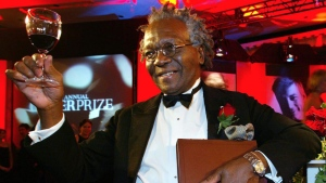 Giller Prize winner Austin Clarke hoists a glass as he holds a copy of his book the Polished Hoe after winning the $25,000 literary prize at the Four Seasons Hotel in Toronto, November 5, 2002. (Kevin Frayer / THE CANADIAN PRESS)