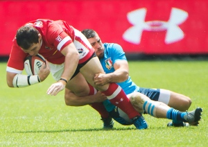 Canada's Aaron Carpenter, left, gets tackled by Italy's Edoardo Gori, right, during first half summer series rugby action, in Toronto on Sunday, June 26, 2016. (THE CANADIAN PRESS/Nathan Denette)