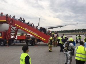 This image provided by Lee Bee Yee shows passengers disembarking a Singapore Airlines flight after an engine fire, at Changi International Airport in Singapore on Monday, June 27, 2016. (Lee Bee Yee via AP)