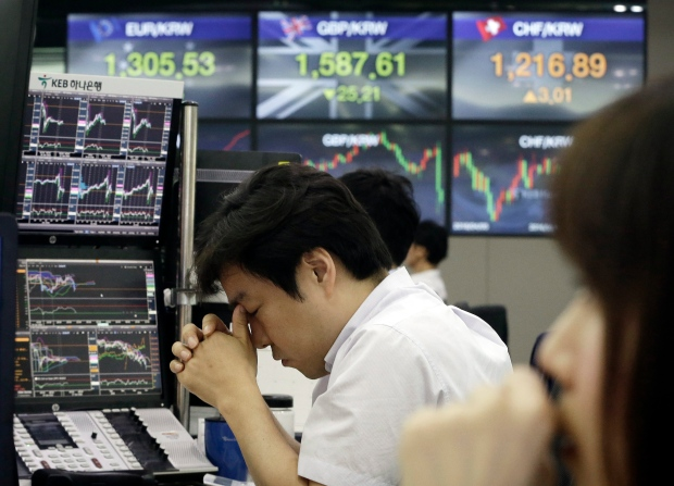 A currency trader rubs his eyes at the foreign exchange dealing room of the KEB Hana Bank headquarters in Seoul, South Korea, Monday, June 27, 2016. (AP Photo/Ahn Young-joon)