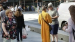 A man wearing an orange robe talks with a woman in New York's Times Square on Friday, June 24, 2016. (AP / Mark Lennihan)