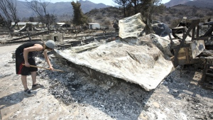 Nathan Looper uses a hoe to sift through the ashes of the home of his stepfather, Lucas Martin in South Lake, Calif. on Sunday, June 26, 2016. (AP / Rich Pedroncelli)