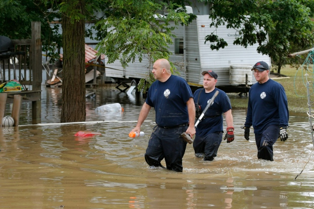 Bridgeport W.Va. firefighters, Steve Gallo, left, and Ryan Moran, centre, are joined by an unidentified co-worker as they walk through a flooded street while searching homes in Rainelle, W. Va., Saturday, June 25, 2016. (AP Photo/Steve Helber)