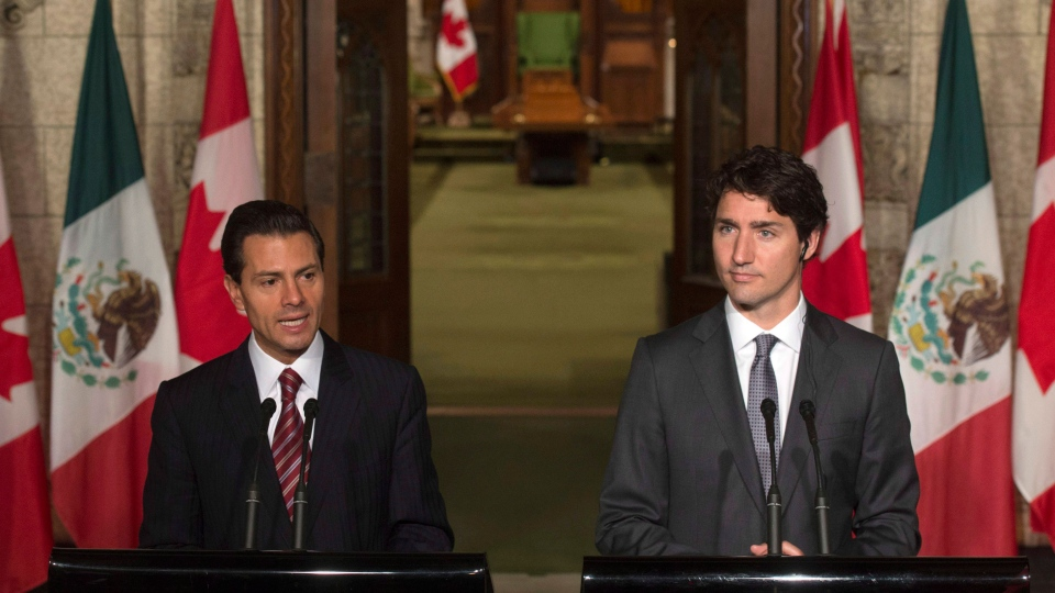 Canadian Prime Minister Justin Trudeau (right) listens to Mexican President Enrique Pena Nieto respond to a question during a joint news conference on Parliament Hill in Ottawa, Tuesday, June 28, 2016. THE CANADIAN PRESS/Adrian Wyld