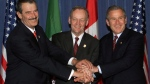 Mexican President Vicente Fox, Canadian Prime Minister Jean Chretien and U.S. President George W. Bush clasp their hands together after a meeting between the three leaders after the closing of the Summit of the Americas in Quebec City, April 22, 2001. (THE CANADIAN PRESS / Tom Hanson)