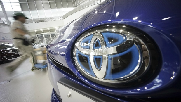 A worker walks past a Toyota car at a Toyota showroom in Tokyo on Wednesday, June 29, 2016. (AP / Eugene Hoshiko)
