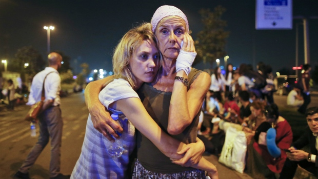 Passengers embrace each other as they wait outside Istanbul's Ataturk airport following their evacuation after a blast early Wednesday, June 29, 2016. (AP P/ Emrah Gurel)