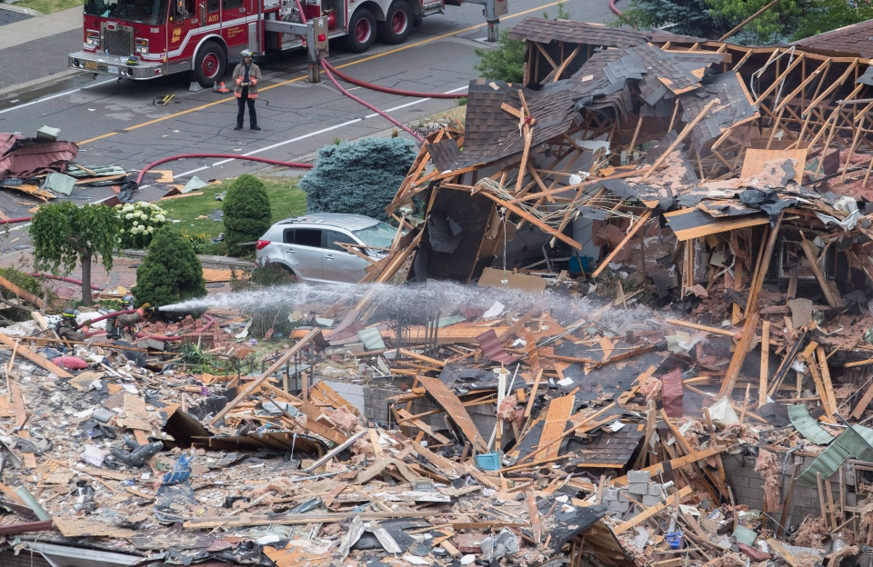 A firefighter sprays water on a debris litter street after a house explosion in Mississauga, Ont., Tuesday, June 28, 2016. THE CANADIAN PRESS/ Mark Blinch