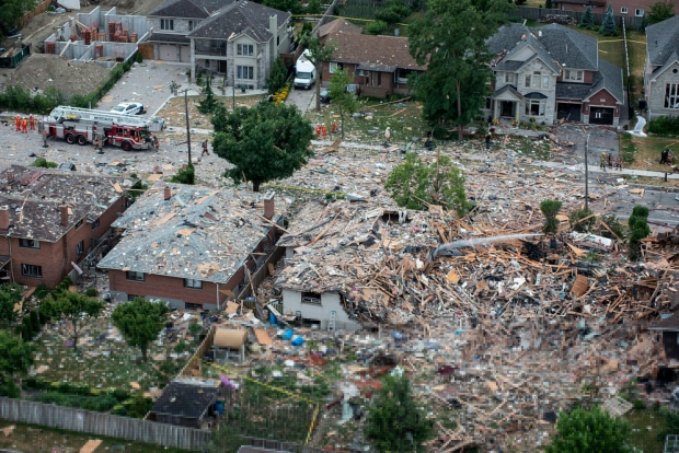 Firefighters examine debris after a house explosion in Mississauga, Ont., Tuesday, June 28, 2016. THE CANADIAN PRESS/Eduardo Lima