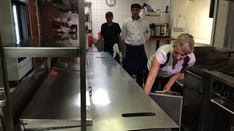 Manitoba Public Health Inspector Natalie Lowdon checking the temperature of a cooler at a Corydon Ave. restaurant.