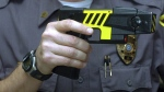 An officer holds a stun gun used by his police department in a Farmington, Conn. on Oct. 28, 2004. (AP / Bob Child)