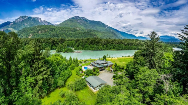 This sprawling 13-acre waterfront estate includes five bedrooms and six bathrooms, as well as floor-to-ceiling windows and a vaulted master suite. <br><br> Listed at $5,999,800, the Squamish mansion boasts a gourmet kitchen, covered outdoor patio and salt water pool, with views of the mountains and the Squamish River. (Photos from soprovich.com)