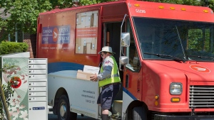 A Canada Post employee fills a community mail box in Dartmouth, N.S. on Thursday, June 30, 2016. THE CANADIAN PRESS/Andrew Vaughan