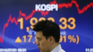 A currency trader looks at the monitors near a screen showing the Korea Composite Stock Price Index (KOSPI) at the foreign exchange dealing room in Seoul, South Korea on Friday, July 1, 2016. (AP / Lee Jin-man)