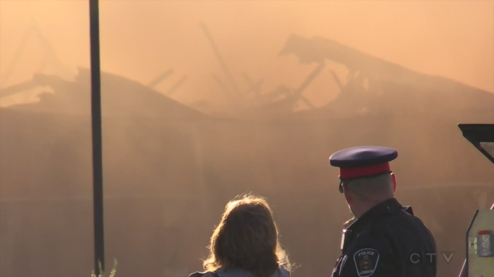 Citizens and police watch on as fire destroys a business plaza in Hyde Park of London, Ont, on Thursday, June 30, 2016. (Marek Sutherland / CTV London)