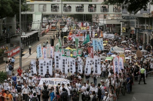 Hundreds of protesters march on a downtown street during the annual pro-democracy protest in Hong Kong, Friday, July 1, 2016. (AP Photo/Kin Cheung)