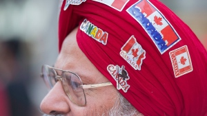A man wears patriotic stickers on his turban as he particpates in the annual Canada Day parade in Montreal, Friday, July 1, 2016. THE CANADIAN PRESS/Graham Hughes