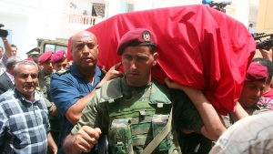 Family, friends and officers carry the Tunisian flag-draped coffin of the head of the pediatric service at the Tunis military hospital, Col. Fathi Bayoudh, one of the victims killed Tuesday at the blasts in Istanbul's Ataturk airport, during his funeral in Ksour Essaf, southern Tunisia, on Friday, July 1, 2016. (AP Photo/Hassene Dridi)