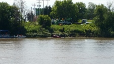 Tow trucks pull vehicle from river