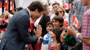 Prime Minister Justin Trudeau high fives children of a Syrian refugee family during Canada Day celebrations on Parliament Hill, in Ottawa on Friday, July 1, 2016. (Justin Tang / THE CANADIAN PRESS)